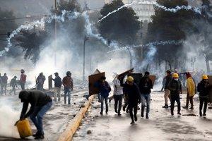 AME9172. QUITO (ECUADOR), 13/10/2019.- Manifestantes corren entre los gases lacrimógenos lanzados por la policía en una nueva jornada de choques este domingo, en Quito (Ecuador). Las protestas comenzaron el 3 de octubre contra las medidas de austeridad económicas adoptadas por el Gobierno, especialmente la eliminación de los subsidios a los combustibles, como parte de las condiciones puestas por el Fondo Monetario Internacional (FMI) y otras instituciones para un crédito de 10.000 millones de dólares. EFE/ Paolo Aguilar