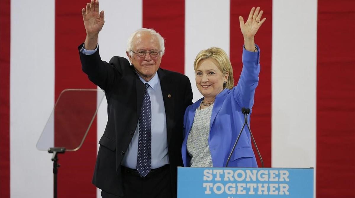 Sanders y Clinton saludan juntos a la audiencia del acto celebrado en Portsmouth (Nuevo Hampshire), este martes.