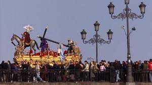 Una procesión de Semana Santa en Sevilla cruza por el puente de Triana.