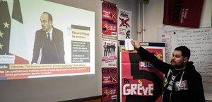 Un sindicalista ferroviario escucha la comparecencia del primer ministro francés, Edouard Philippe, sobre la reforma de las pensiones.