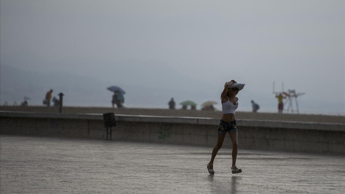 Una joven se protege de la lluvia en la playa del Fòrum, en Barcelona.