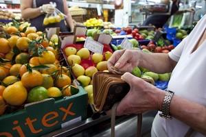Una mujer llena la cesta de la compra en un mercado de Barcelona.