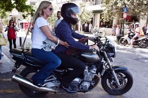 El ya exministro de Finanzas griego, Yanis Varoufakis, y su mujer, Danae Stratou, encima de una moto a la puerta de su casa, en Atenas.