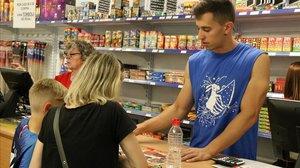 Un vendedor de una tienda de petardos atendiendo a unos clientes.