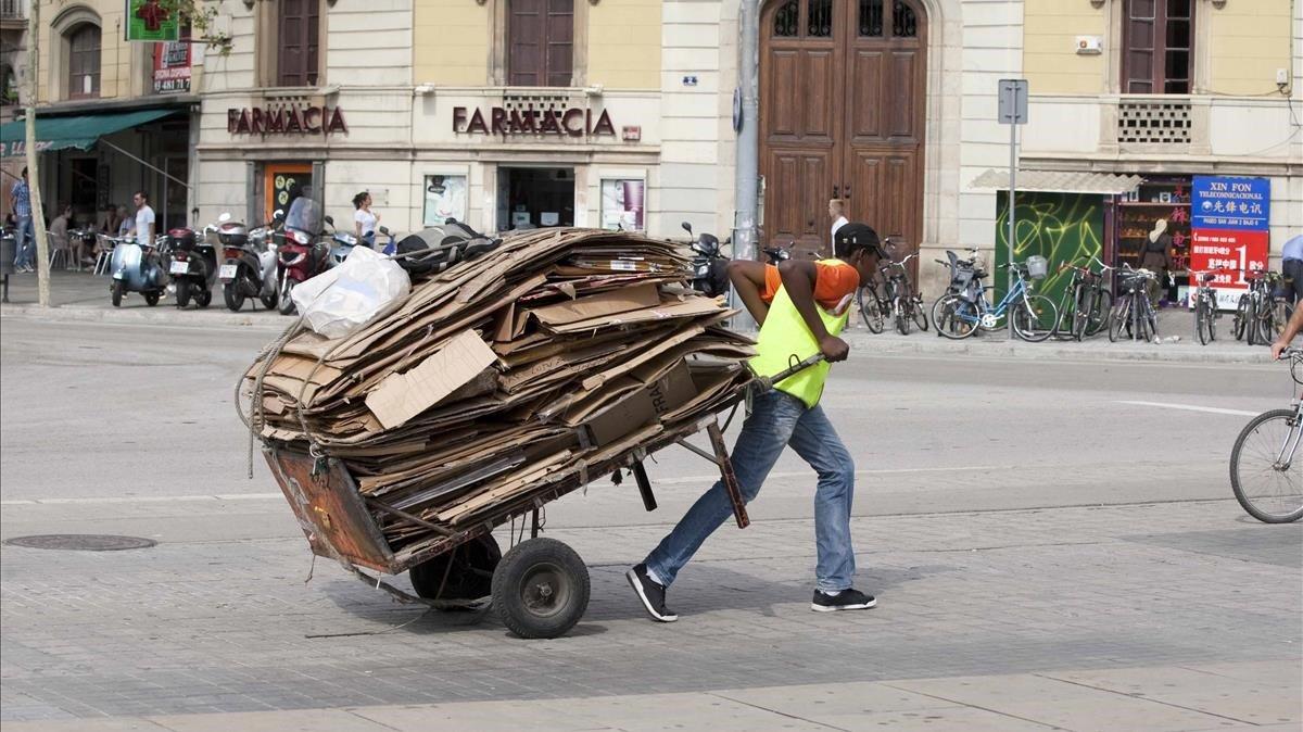 Un nmigrante africano lleva un carrito lleno de cartones.