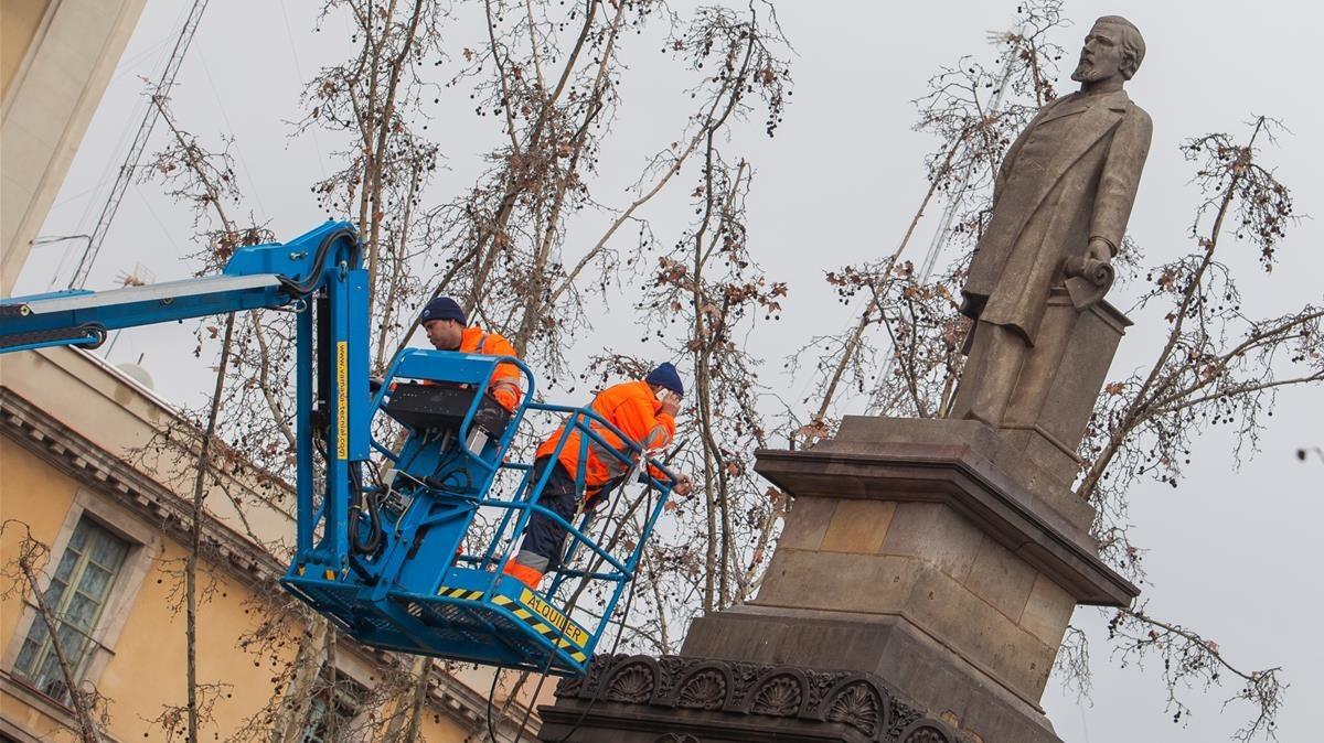 Unos operarios limpian la estatua de Antonio López, este jueves.
