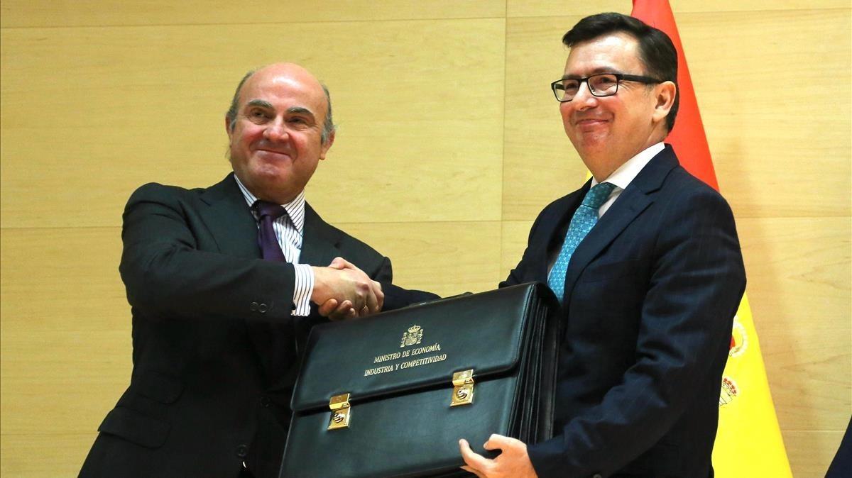 El nuevo ministro de Economía, Román Escolano, recibiendo su cartera de manos de su antecesor, Luis de Guindos, este viernes en Madrid.