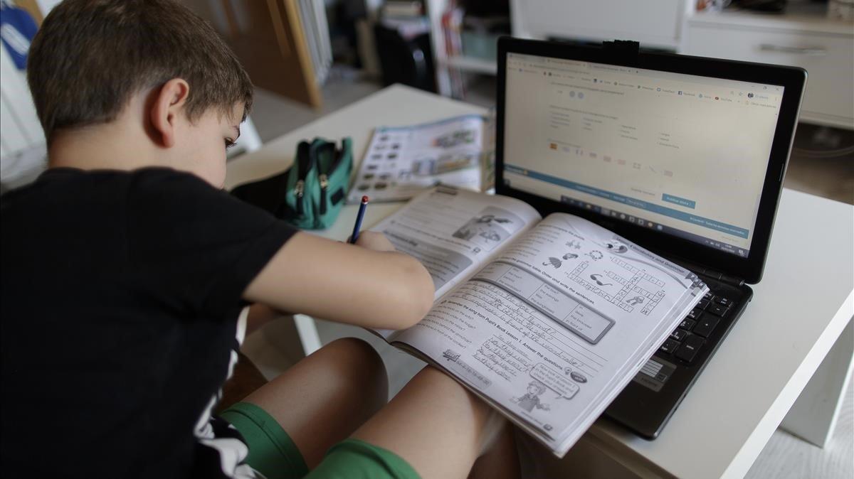 Un niño realiza sus deberes con un portátilen su casa, durante el confinamento.