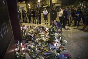 Los parisinos dejan flores y velas en honor a las víctimas de los atentados, en el café Carillon, en París.