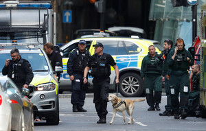 Police officers and ambulance crews stand outside Borough Market after an attack left 6 people dead and dozens injured in London