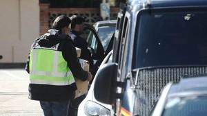 Agentes retirando cajas de una vivienda registrada durante la operación Miro en Algeciras.