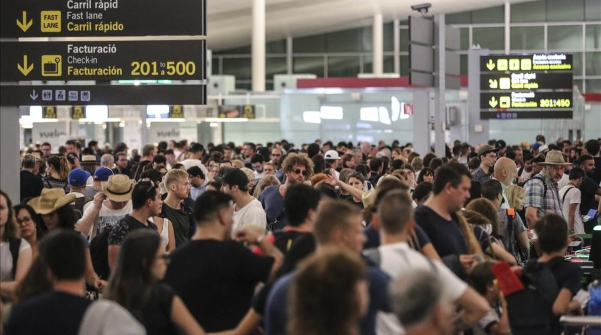 Aglomeración de viajeros en los controles de seguridad de la T-1 del aeropuerto de El Prat, el viernes.