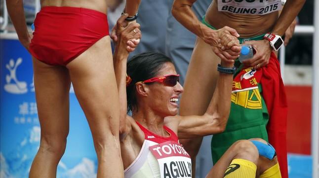 Aguilar es ayudada por otras atletas tras el maratón femenino.