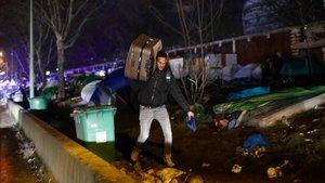 Un refugiado carga con sus pertenencias durante la operación de desalojo del campamento deLa Porte d'Aubervilliers, enParis.
