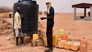 Dos refugiados recogen agua en un tanque en un campo de Níger.
