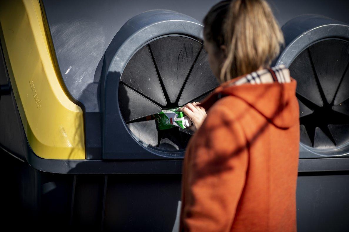 Una persona recicla en el contenedor correspondiente.