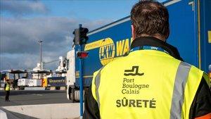 Un empleado de seguridad del puerto de Calais observa un camión.