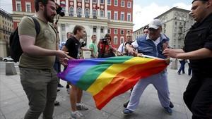 Un hombre intenta arrebatar una bandera de la comunidad homosexual a unos manifestantes en Moscú en el 2015.