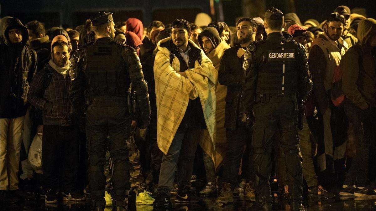 Un grupo de foráneos esperan un autobús para su traslado durante una operación de desalojo de campamentos de migrantes en París.
