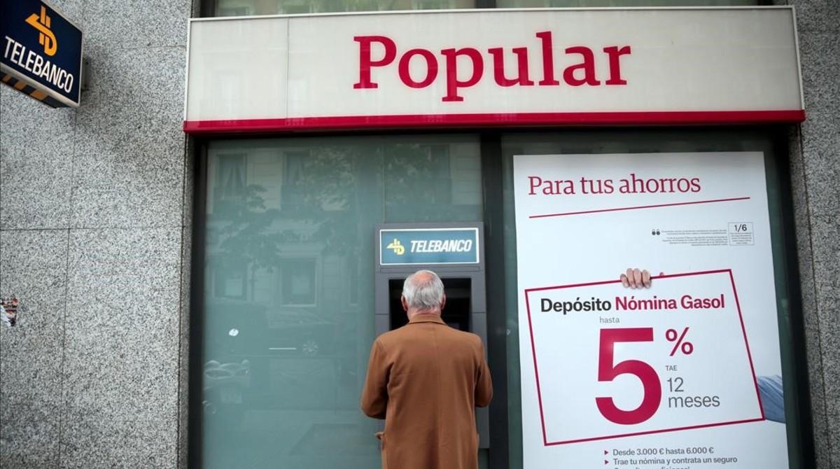 Un hombre saca dinero de un cajero del Popular en Madrid.