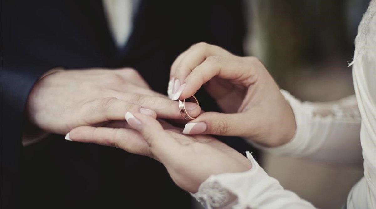 Imagen de una pareja poniéndose los anillos.