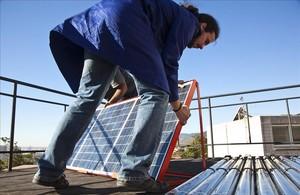 Un hombre instala placas fotovoltaicas en la cubierta de un edificio.