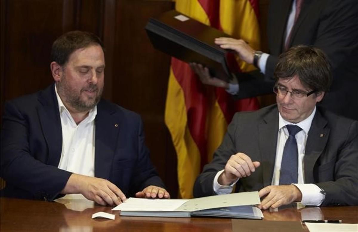 El president de la Generalitat, Carles Puigdemont, junto al vicepresident Oriol Junqueras, durante la firma del decreto de convocatoria del referéndum.