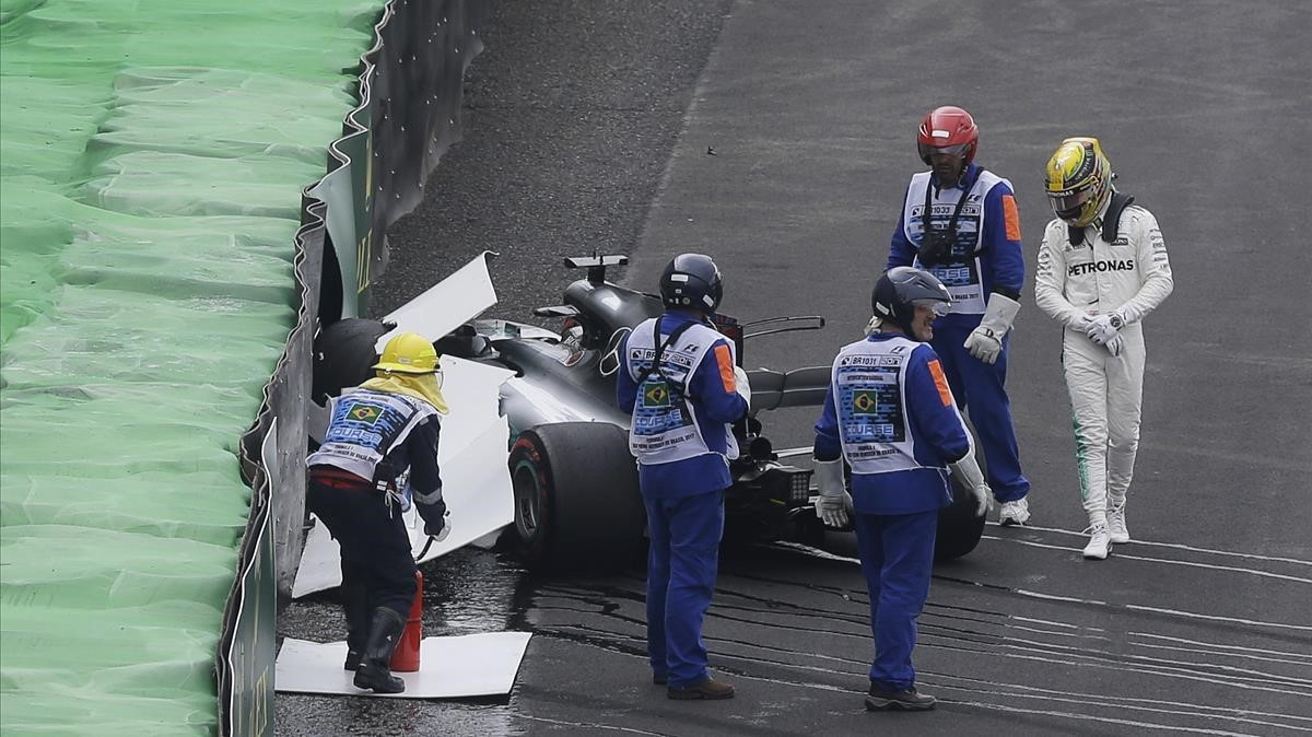 Lewis Hamilton, al lado de su Mercedes siniestrado.