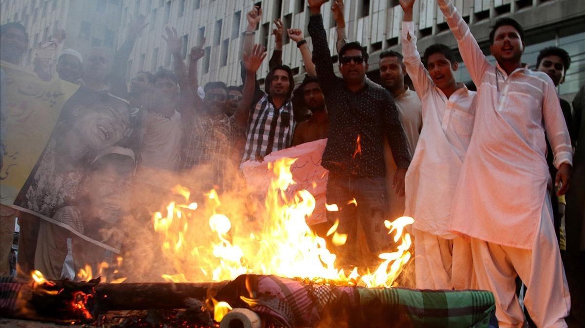 Manifestantes queman una imagen de la líder de facto de Birmania, Aung San Suu Kyi, durante una protesta contra la persecución de los rohinyas, en Karachi (Pakistán), el 17 de septiembre.