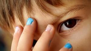 Un niño de cuatro años muestra sus uñas pintadas de azul y purpurina.