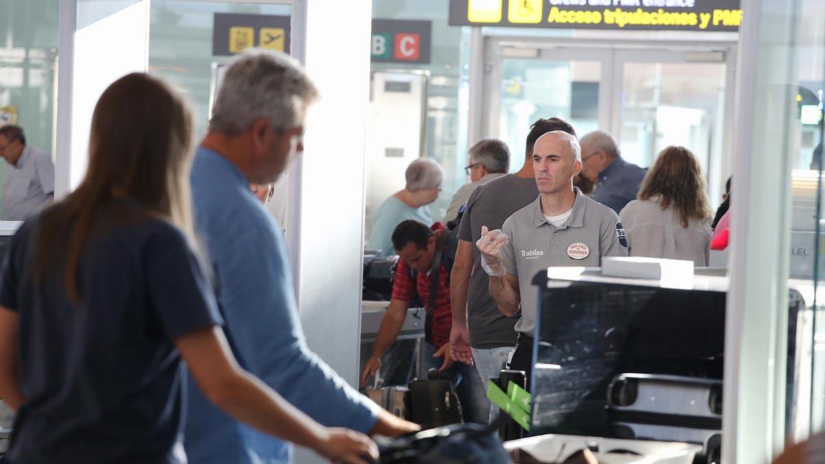 Pasajeros hacen cola para pasar el control de seguridad en el aeropuerto de El Prat.