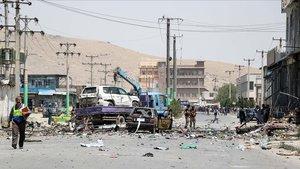Personal de seguridad afgano retiraun vehículo dañado enun atentado suicida en Kabul el 25 de julio de 2019