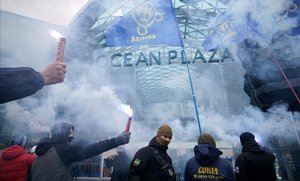 Simpatizantes ucranianos de ultraderecha queman bengalas en Kiev mientras bloquean el acceso al centro comercial Ocean Plaza, del oligarca ruso Boris Rotenberg, una figura cercana a Vladimir Putin.