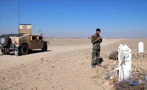 Un soldado afgano reza cerca de una tumba en la provincia de Helmand, este martes.