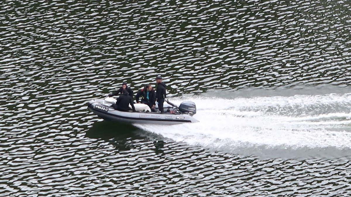 Mossos dEsquadra trasladan uno de los cadáveres localizados en el pantano de Susqueda.