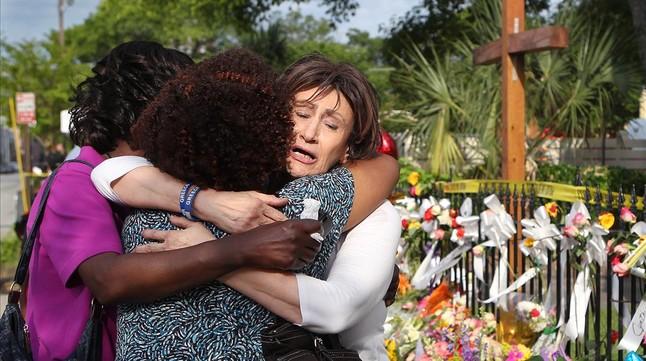Tres mujeres se abrazan junto a la ofrenda floral frente a la iglesia metodista, en Charleston, este sábado.
