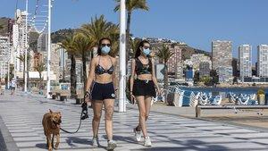 Dos personas paseando por Benidorm, ausente de turistas debido a la emergencia del coronavirus.