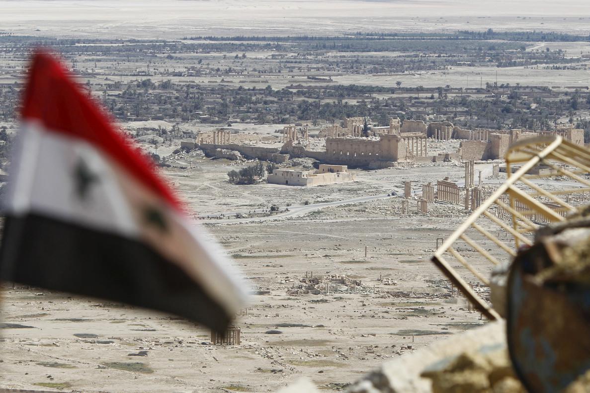 Una bandera siria ondea ante las ruinas de la histórica ciudad de Palmira.