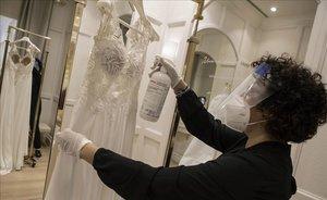 Una empleada de una tienda de Pronovias, en Barcelona, desinfecta un vestido de novia.