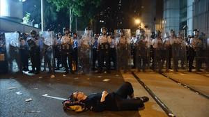 Una manifestante estirada en el suelo bloquea una de las calles de Hong Kong frente a una fila de policías.