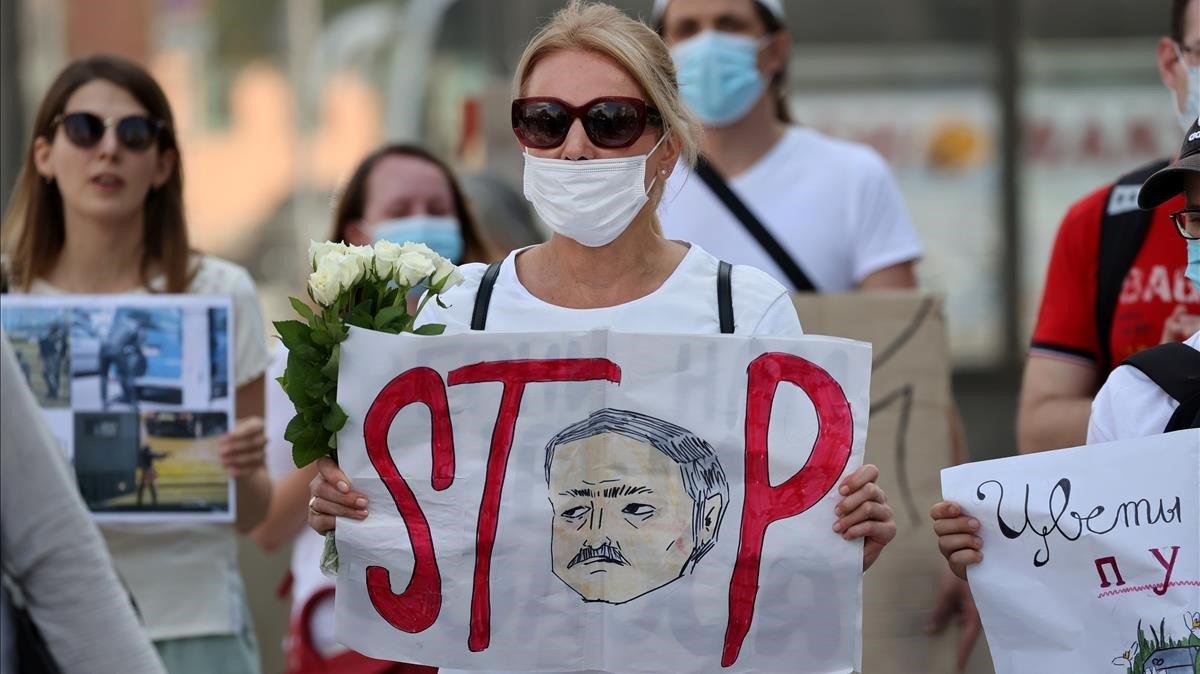 Una manifestante muestra una pancarta en contra de Lukashenko, este sábado en Minsk.