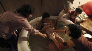 Una mujer da a luz en su casa, dentro de una piscina de agua caliente yrodeada de su familia y otros asistentes.