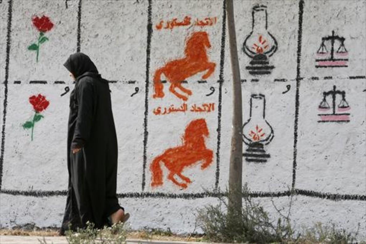 Una mujer pasa en Casablanca ante un muro con pintadas que representan los logotipos de distintos partidos.