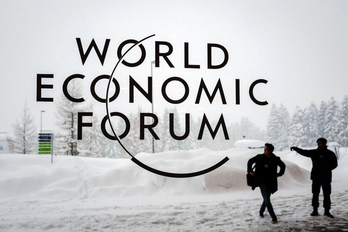 Dos miembros de seguridad frente al cartel del World Economic Forum.