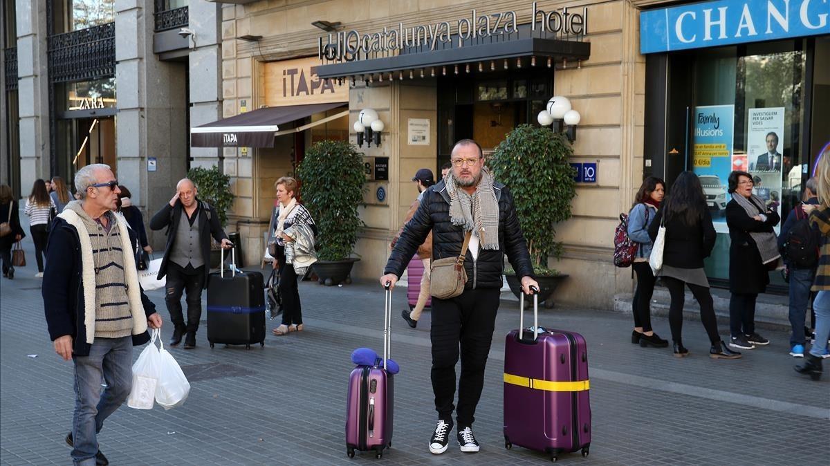Viajeros en la entrada de un hotel en la plaza de Catalunya.