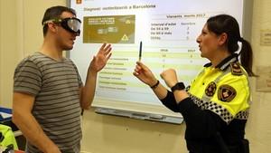 Uno de los asistentes intenta agarrar un bolígrafo con unas gafas que simulan los efectos de la droga en nuestra visión.
