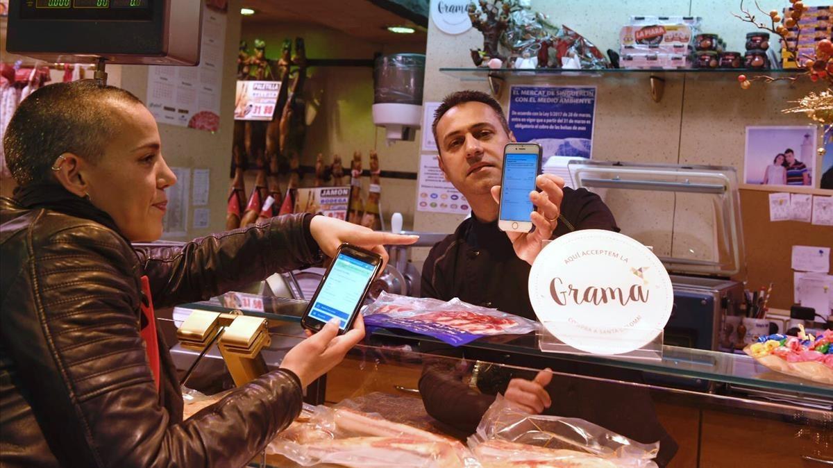 La presidenta de la Agrupació de Comerç de Santa Coloma, Laia Muñoz, simula un pago en la charcutería de Diego Navarro, en el mercado del Singuerlín, este miércoles.