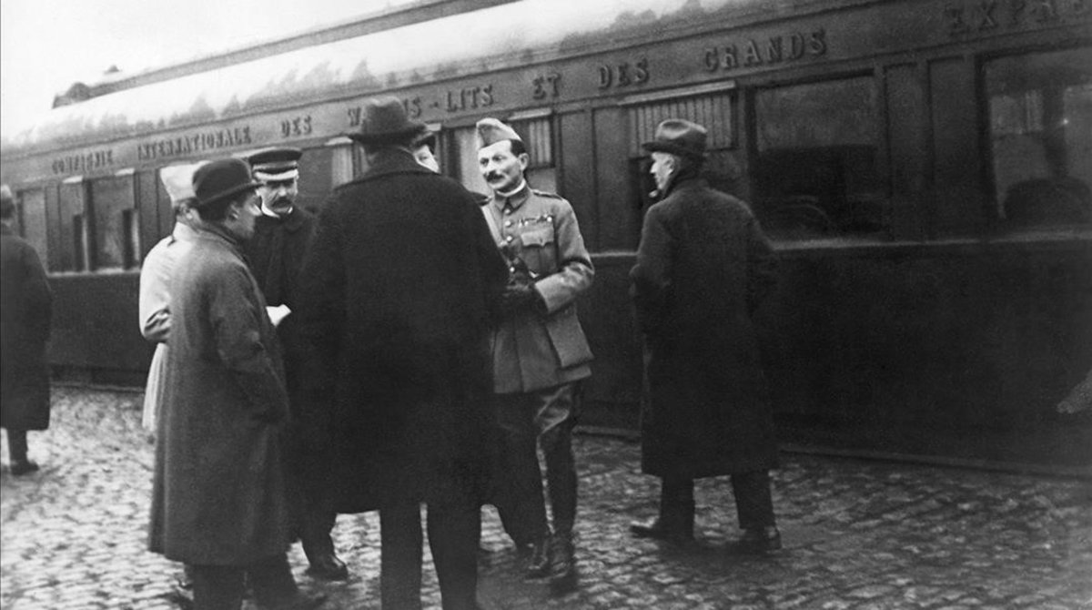 Miembros de las delegaciones alemana y francesa esperan en la estación de Rethondes a entrar en el famoso vagón de Compiegne en el que se firmó el armisticio.
