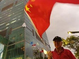 Un jubilado ondea la bandera china a los pies de la torre 101, icono taiwanés.