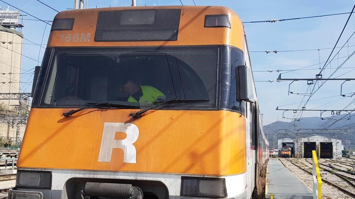 Un operario delservicio de limpieza desinfecta la cabina del maquinista de un tren de Rodalies en Montcada-Bifurcació.